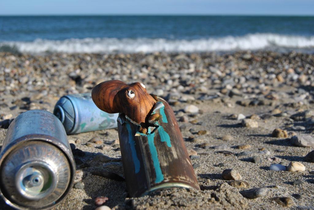Bombe de peinture avec une sculpture de pieuvre posé sur la plage
